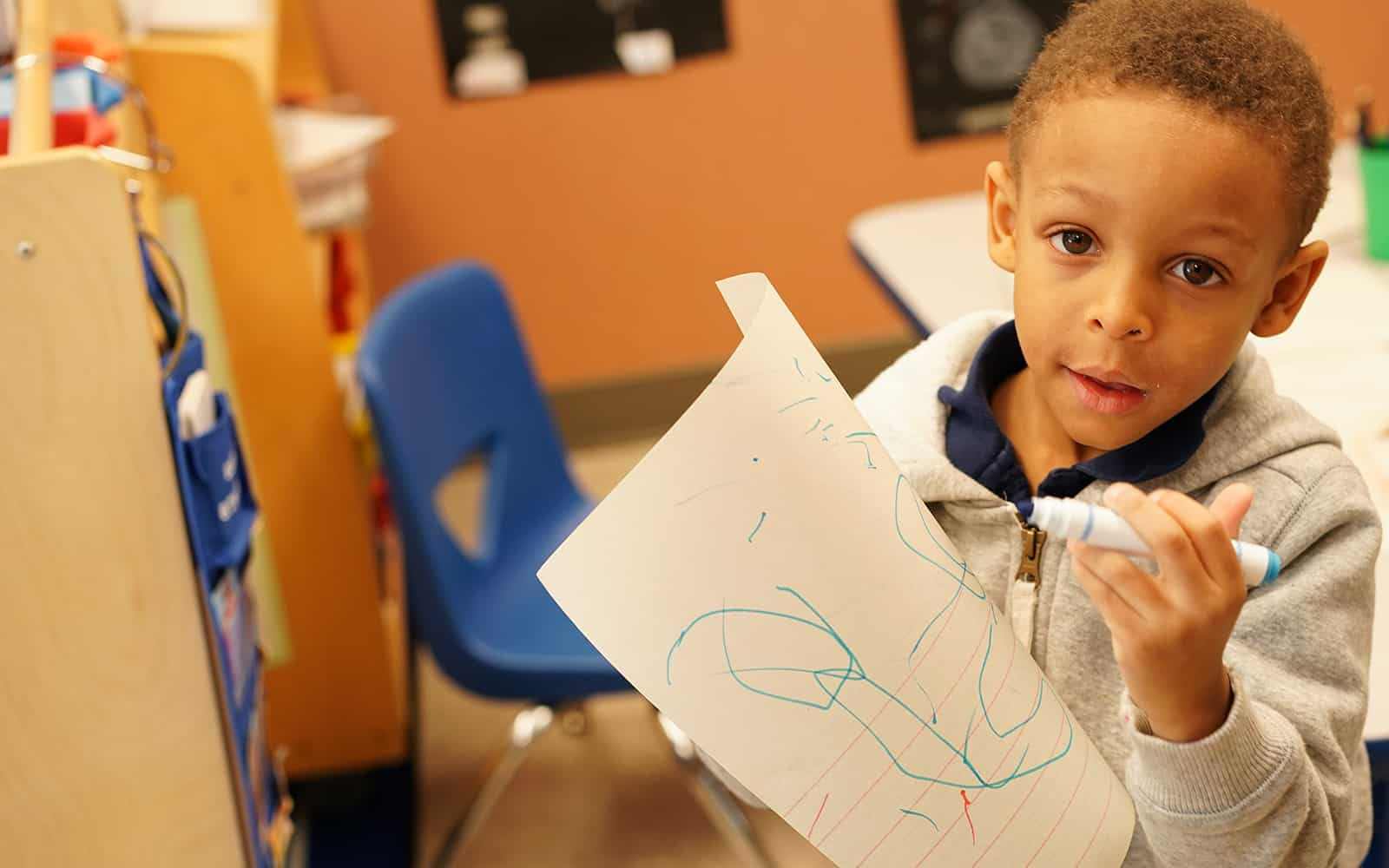 Educare boy drawing on paper with marker