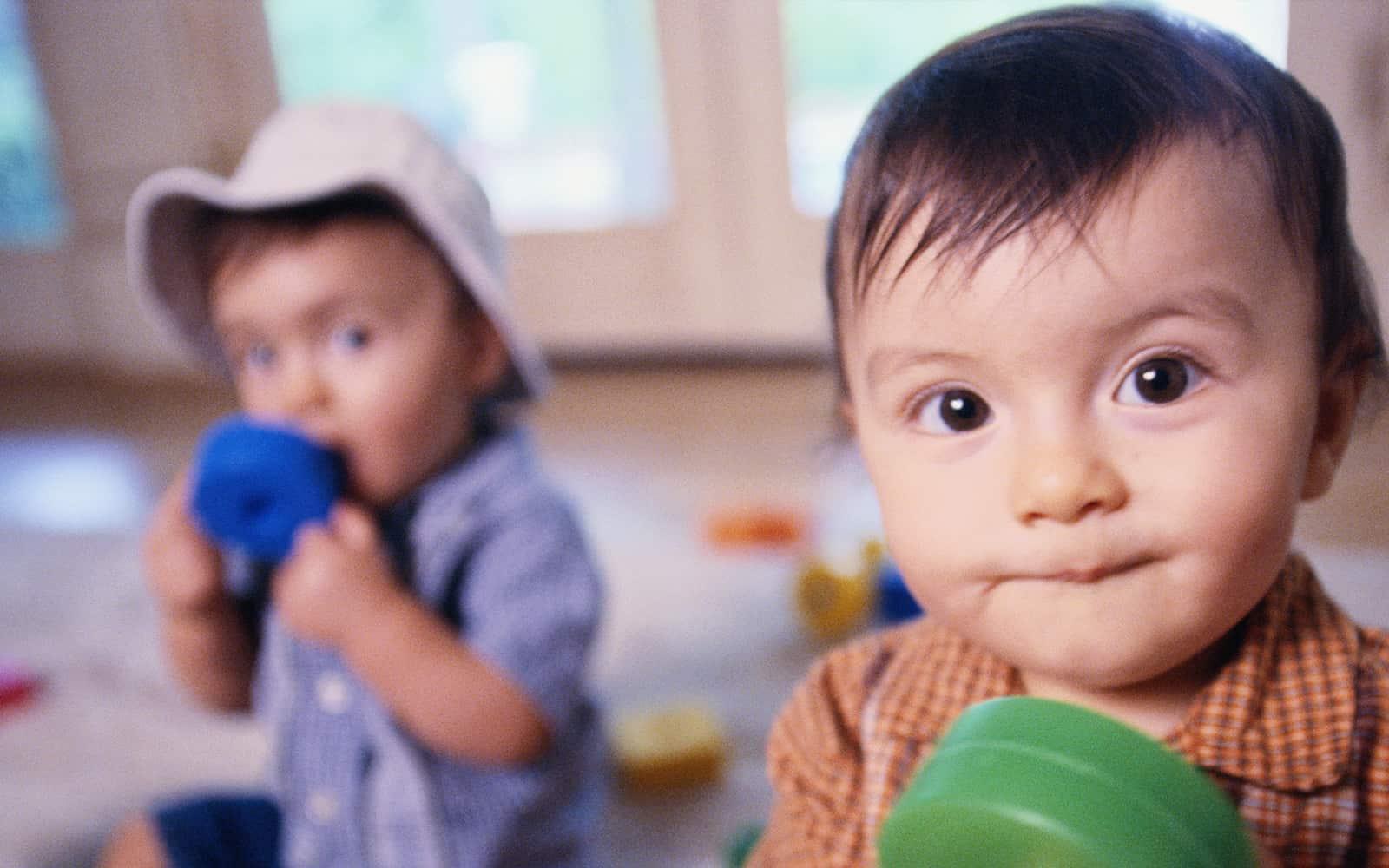 Little boy in orange shirt with green toy