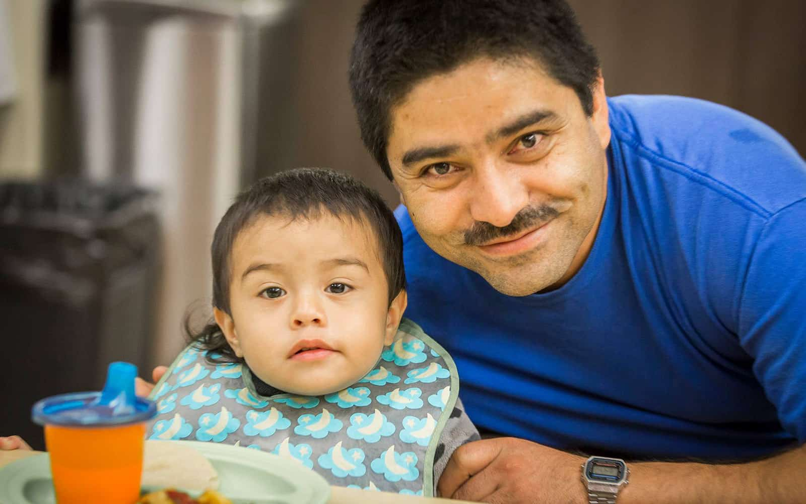 Infant boy eating with dad