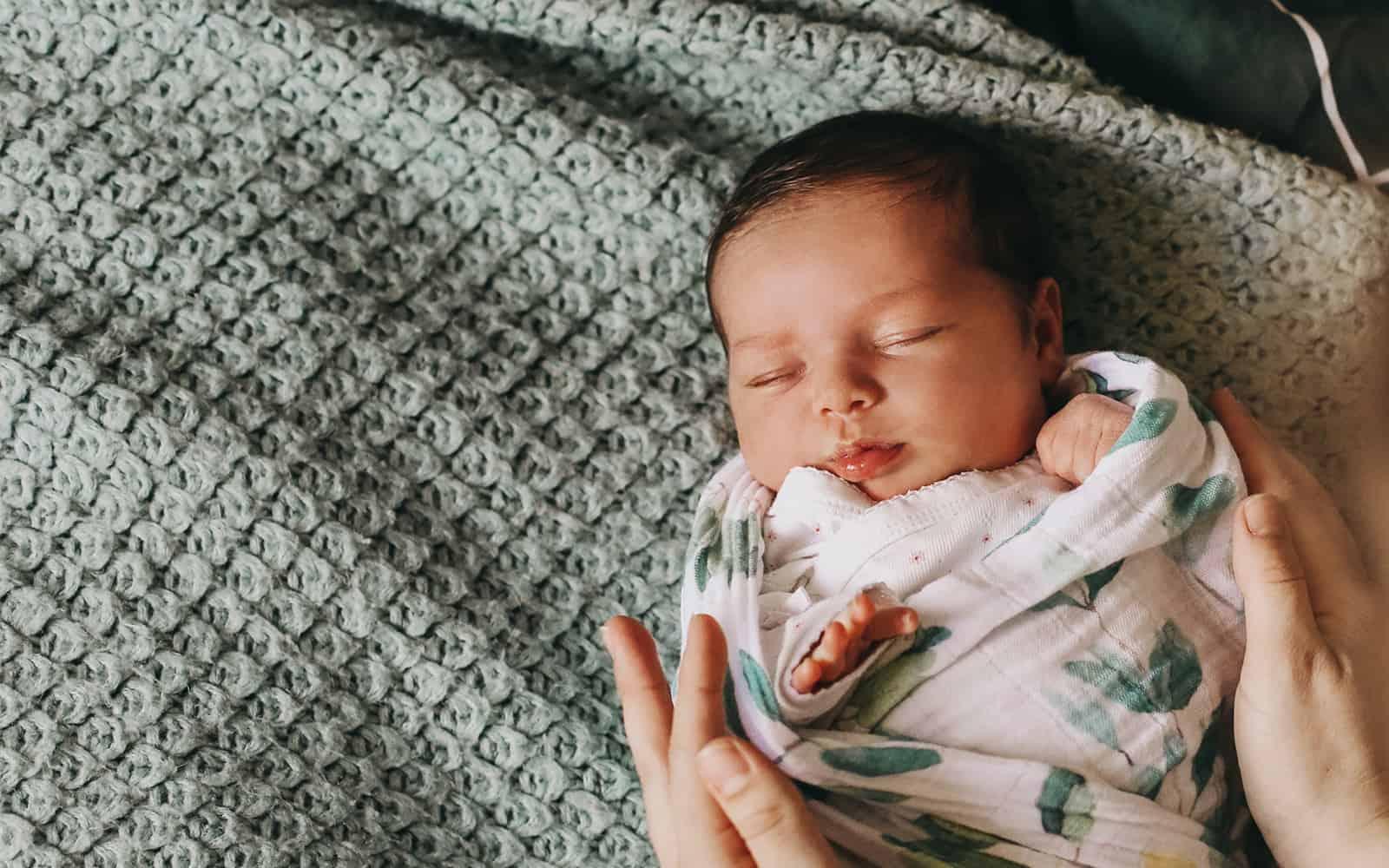 Newborn baby swaddled laying on blanket