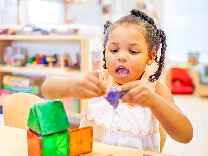 Little girl playing with shapes in classroom