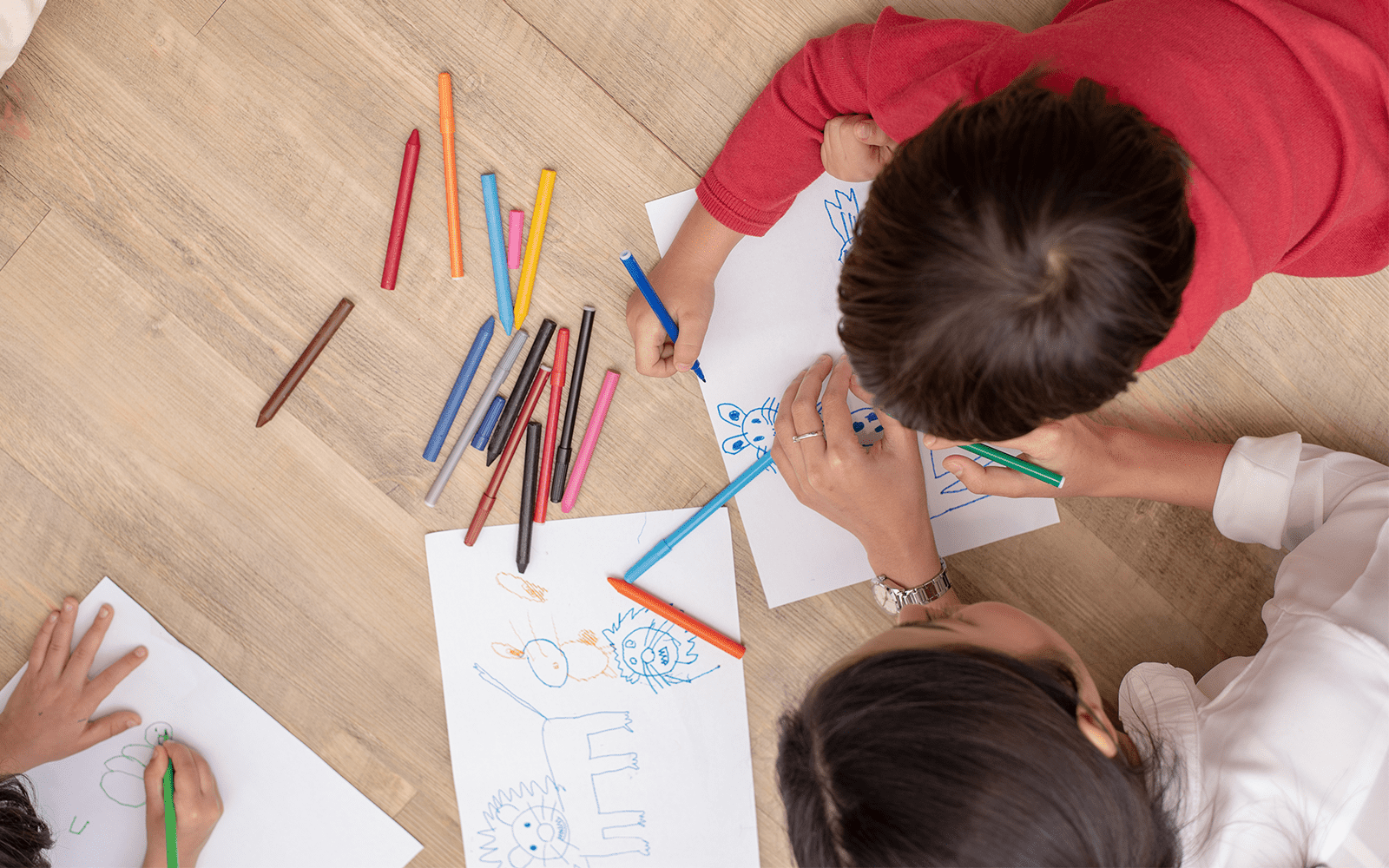 Young child and teacher drawing together