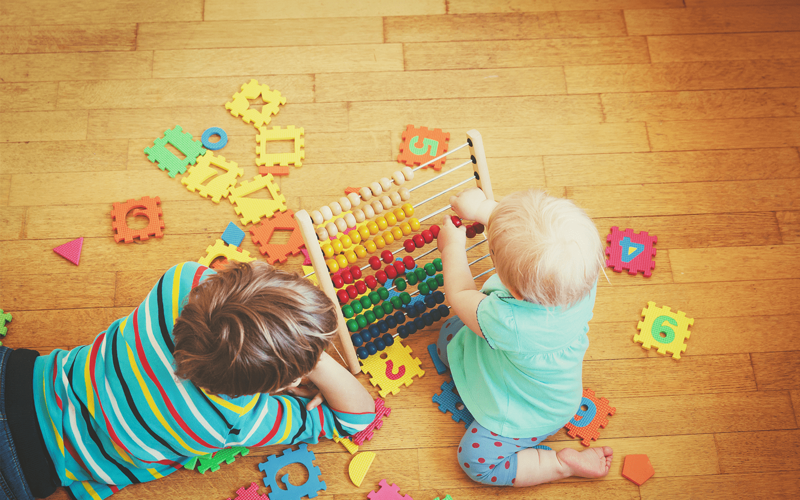 Young child and baby play with early learning toys